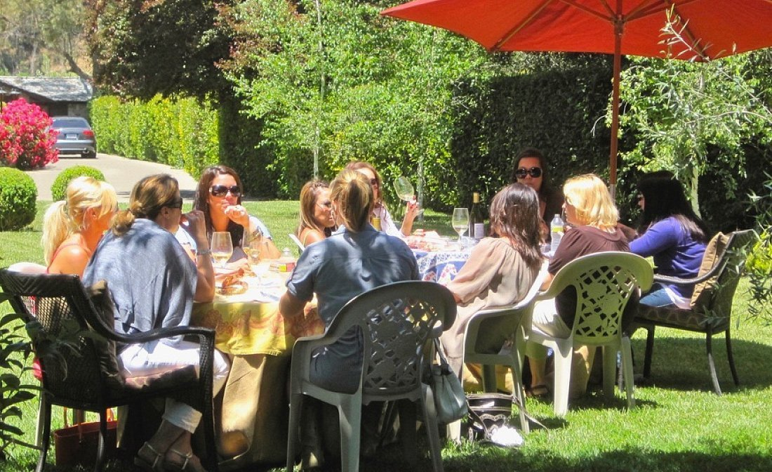 A private wine tasting group seated outside enjoying the private estate.