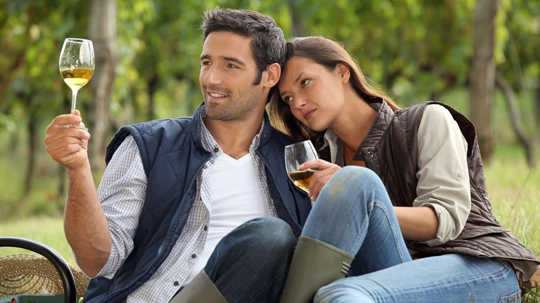 A couple sitting with the male holding up a glass of white wine, they are both looking at the color and clarity before tasting.