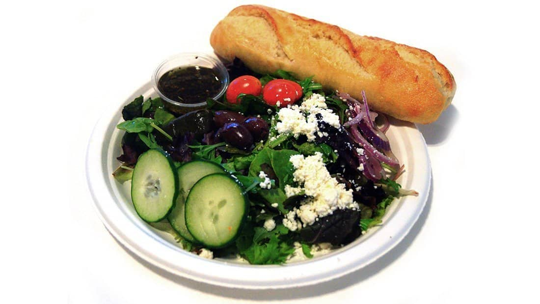 Greek Salad: mixed greens, feta, Greek olives, red onion, cucumber, tomato, and dolma with Greek dressing.