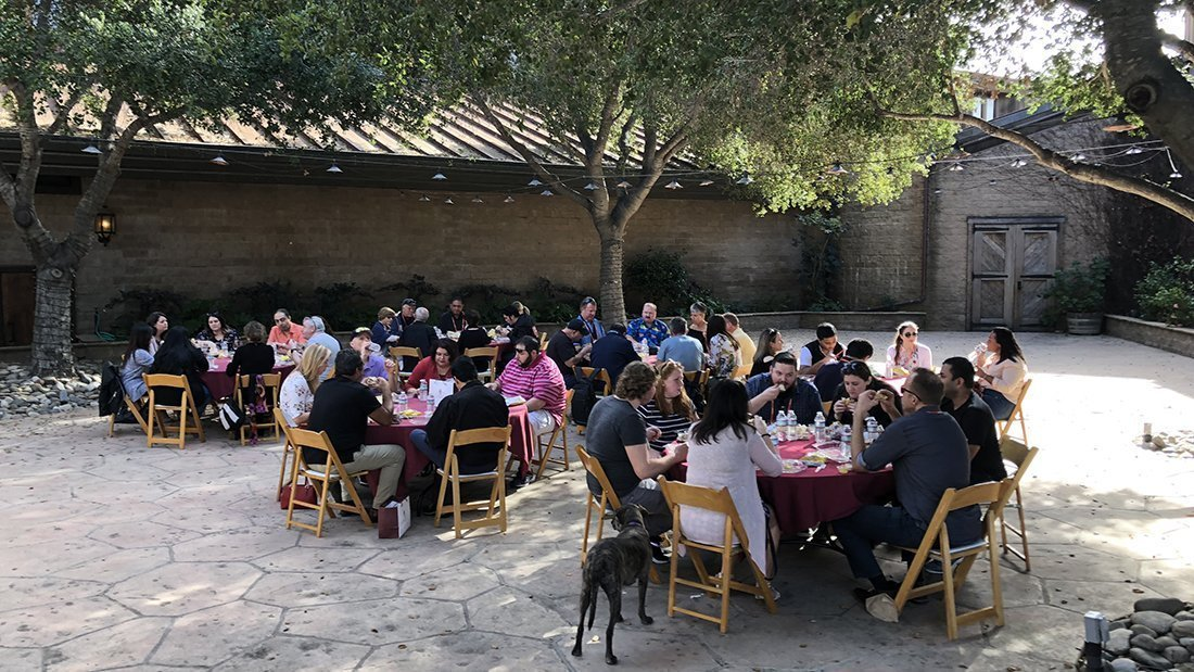 A large group having lunch in the courtyard of a winery.
