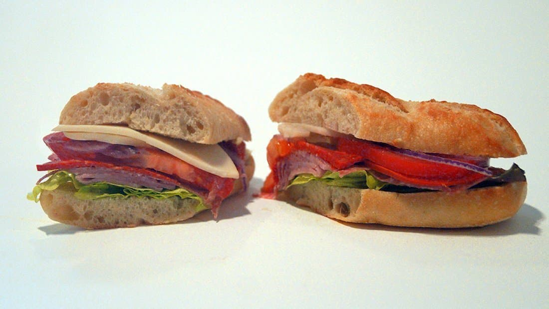 Italian Combo Sandwich: fresh demi-baguette, ham, soppressata, pepperoni, provolone, tomato, red onion, red leaf lettuce, pepperoncinis, and Italian dressing on side.