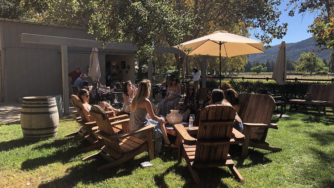 Seated outdoor tasting wines a wine estate.