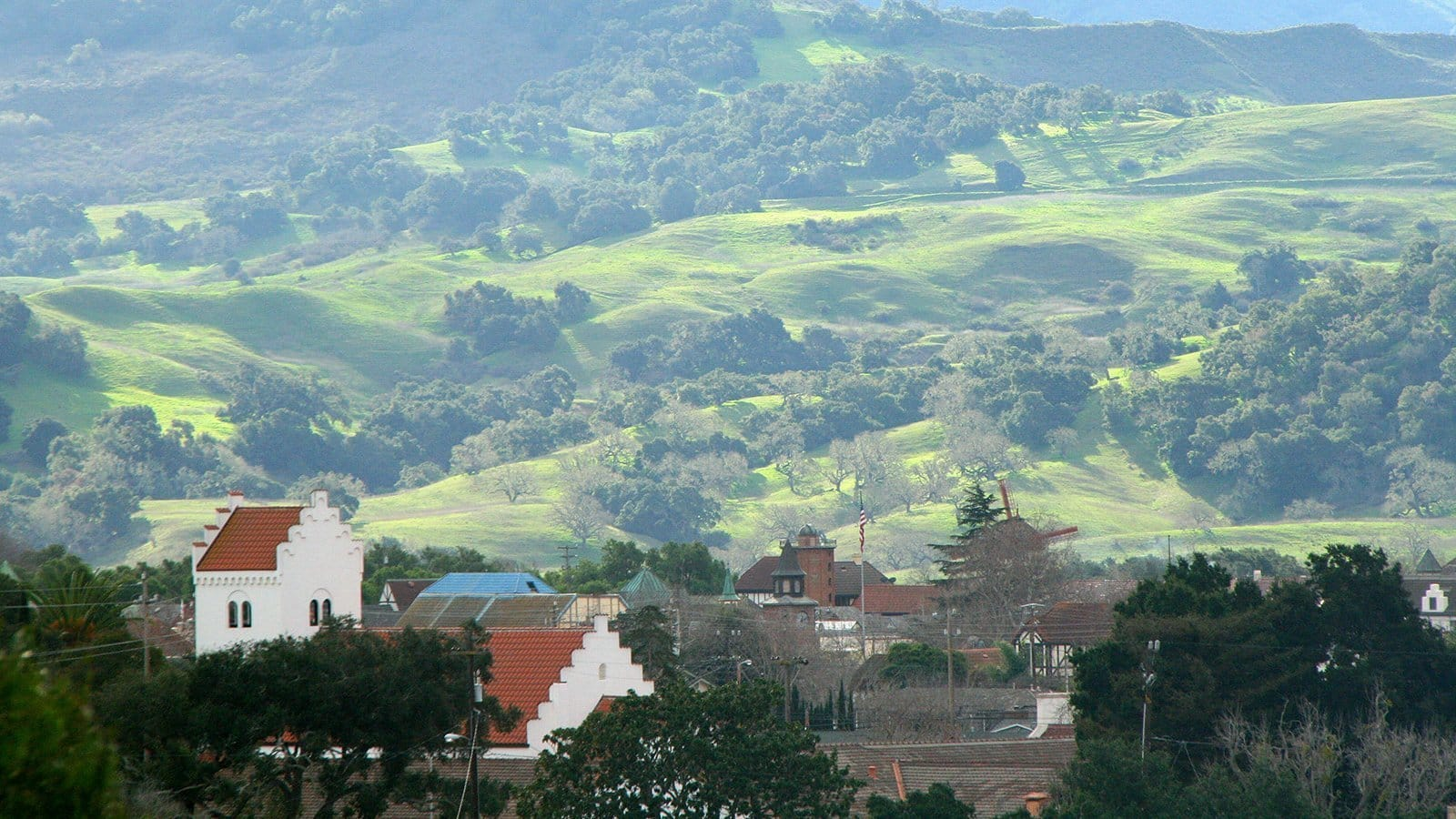 A view of Solvang from a hill above the town. A beautiful picturesque scene with the rolling hills of the Santa Ynez Mountains in the background.