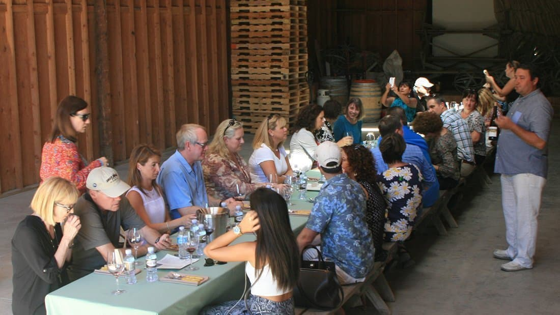A large group sampling wine in a barn on an estate