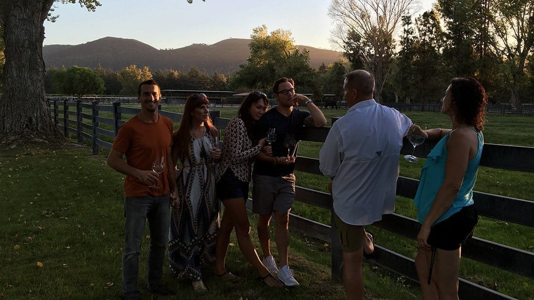 Friends sipping wine at sunset at a private horse ranch and vineyard.