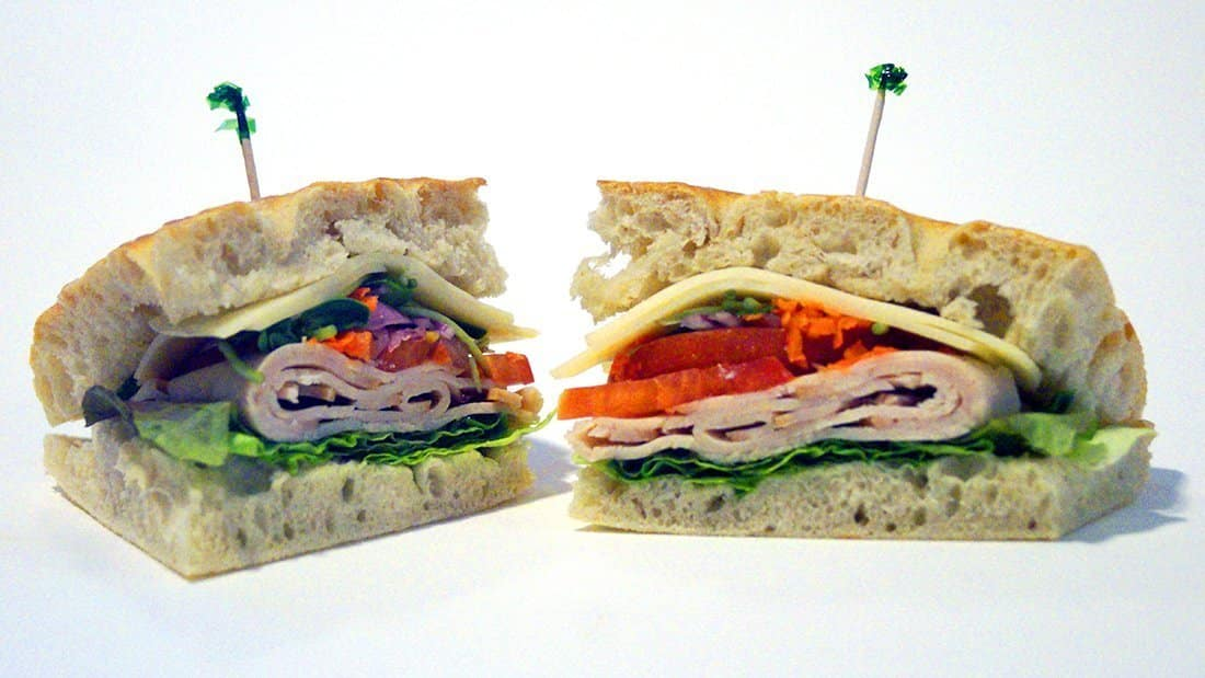 Oven Roasted Turkey Breast Sandwich: fresh focaccia with swiss cheese, lettuce, tomato, sprouts, carrots, cucumbers, and onions.
